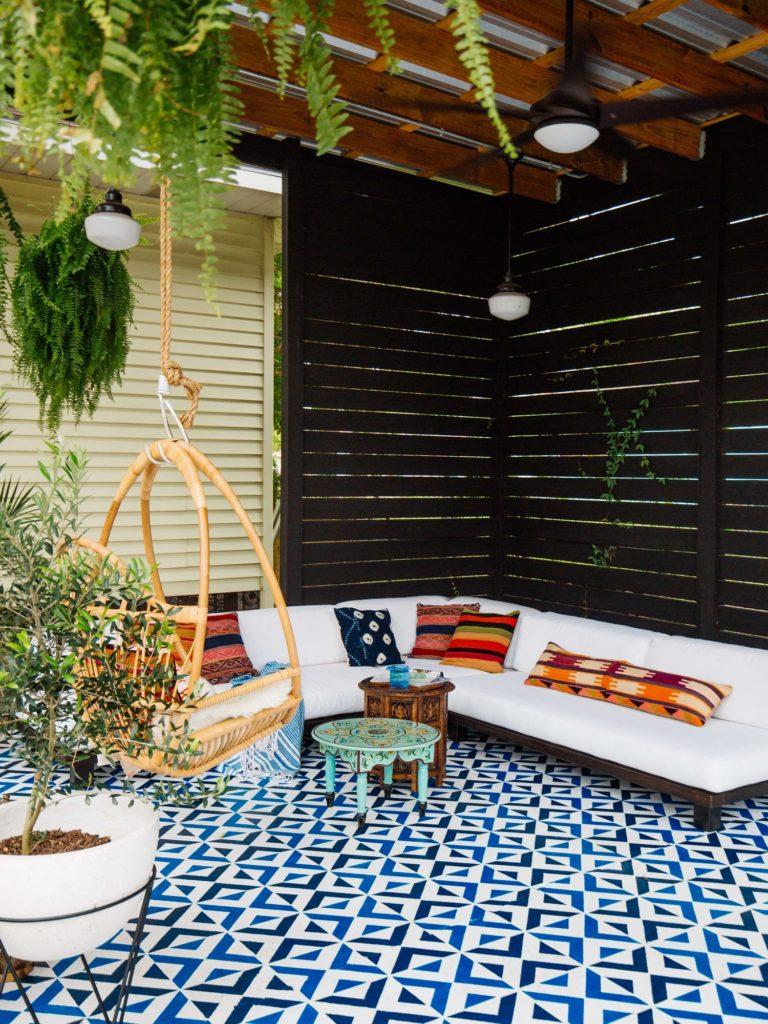 patio decorado con cojines, mesas bajas y plantas