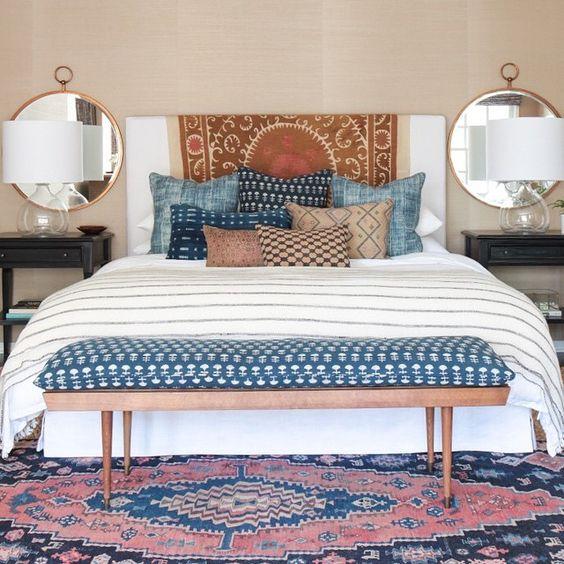 dormitorio con múltiples cojines azules y ocres