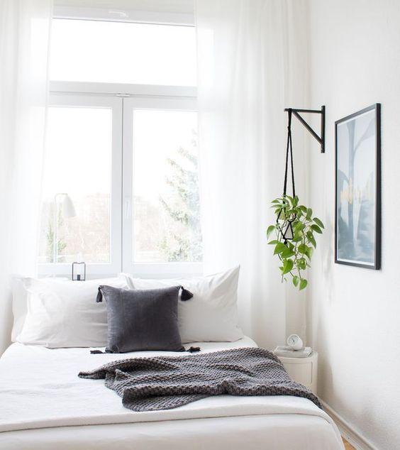 dormitorio con cojines y textil blancos y grises