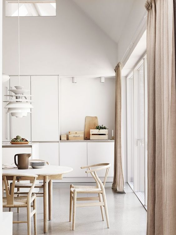 Cocina con silla de madera CH24 y lámpara Poul Henningsen blanca.
