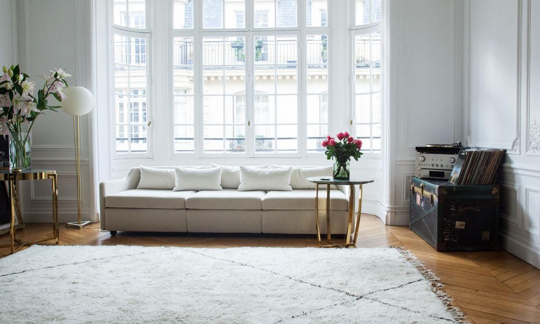 Interior de apartamento parisino con lámpara de pie dorada y blanca, sofá blanco y mesa con pie dorado