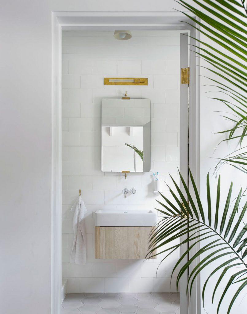 Baño decorado en blanco con plantas